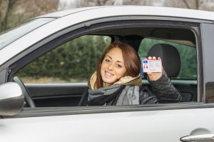girl in the car smiling happy showing her driver's license due to her Dayton Driver's License Reinstatement Attorneys