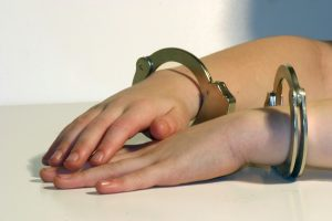 Child's hands in handcuffs resting on table of a person calling a juvenile attorney dayton