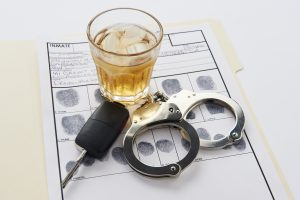 Handcuffs with fingerprints keys and glass of alcohol on ice for a dui defense lawyer troy