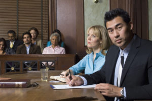 picture of courtroom with lawyer and defendant, contact our top rated Troy criminal defense lawyers