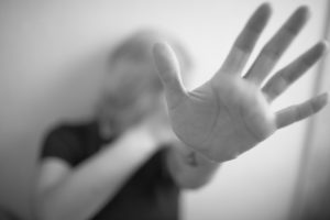 Woman protecting herself with her hands representing how The VanNoy Firm can help you with your domestic violence case