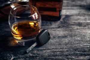 An alcoholic beverage next to some car keys, representing how one should contact a Dayton DUI defense attorney.